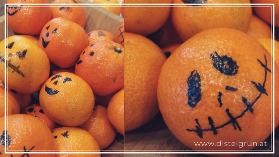 Mandarinen verkleidet als Halloween-Kürbisse